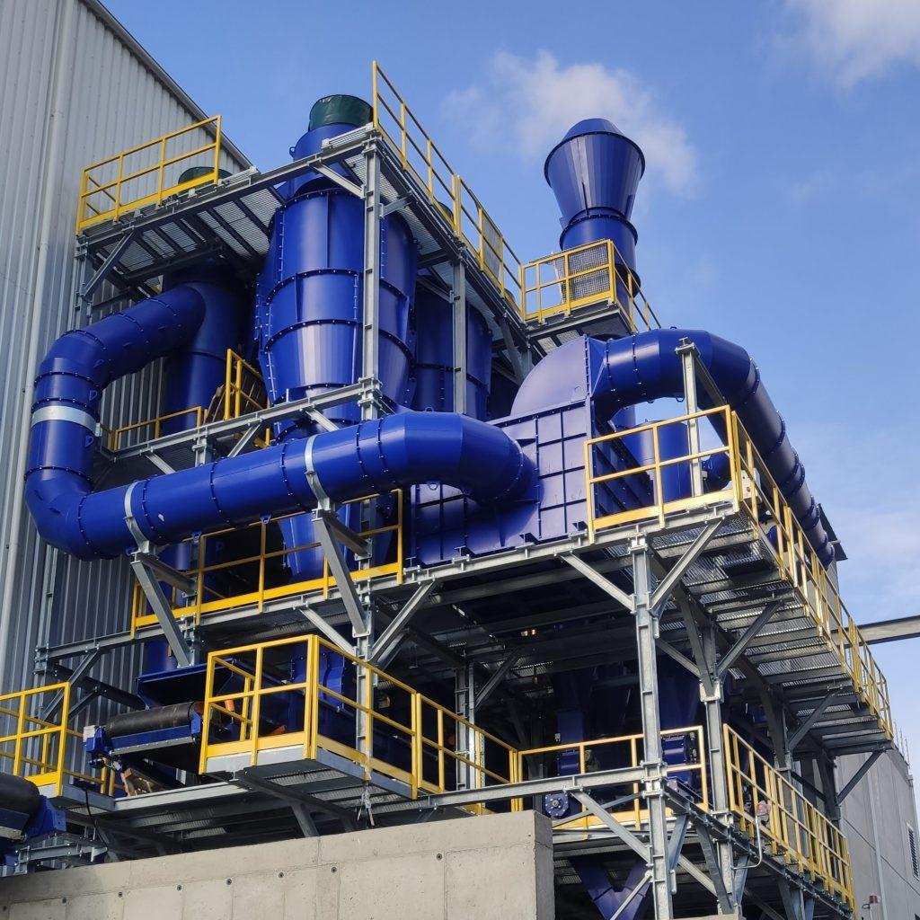 Fabricamos separadores ciclónicos para la separación de polvo. Nuestra línea de productos incluye 22 separadores ciclónicos para una capacidad de 400 m3 / h hasta 30.000 m3 / h. ¡No subestime las posibilidades de utilizar ciclones! ¡Puede ser muy eficaz! Los separadores ciclónicos se utilizan como preseparadores de polvo grueso ubicados frente al dispositivo de filtración final. Su función asegura la separación de la fracción más gruesa antes de ingresar al dispositivo de filtración. Solo la deriva residual fina entra en el filtro. El uso de un separador ciclónico en combinación con un dispositivo de filtro brinda una mayor confiabilidad operativa del sistema, una carga de filtro reducida y una vida útil prolongada del medio filtrante. Los separadores ciclónicos de nuestra producción ya están equipados en la versión básica con una extensión para un vaso de expansión en la salida de polvo. El accesorio más común es el uso de un alimentador giratorio en la descarga de polvo, que separa la sobrepresión o depresión de trabajo dentro del separador del entorno circundante y al mismo tiempo asegura la eliminación del polvo. El separador ciclónico debe colocarse sobre una estructura de acero. El cuerpo del ciclón puede aislarse térmicamente, en el caso de su aplicación a gases de combustión calientes.
